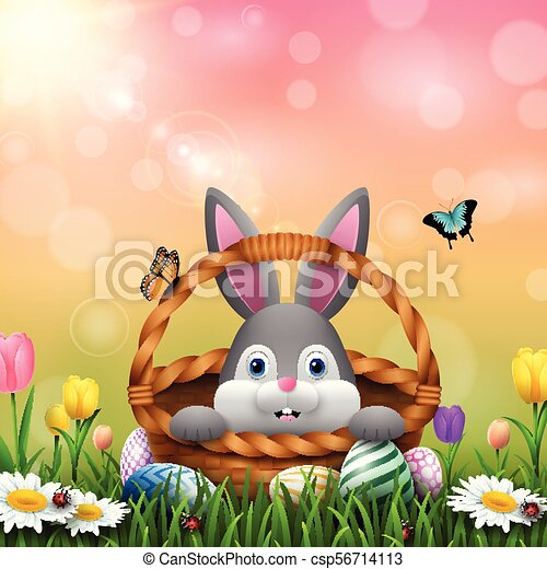 Cute Easter bunny in a basket with colorful eggs on the grass - csp56714113