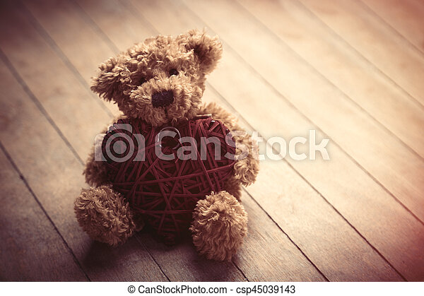 cute fluffy teddy bear with heart shaped toy on the wonderful brown wooden background - csp45039143