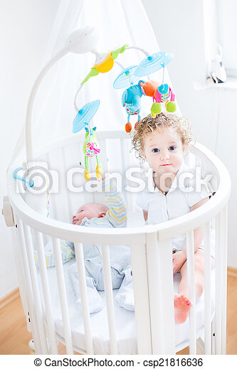 Cute funny toddler girl sitting in a crib of her newborn baby br - csp21816636