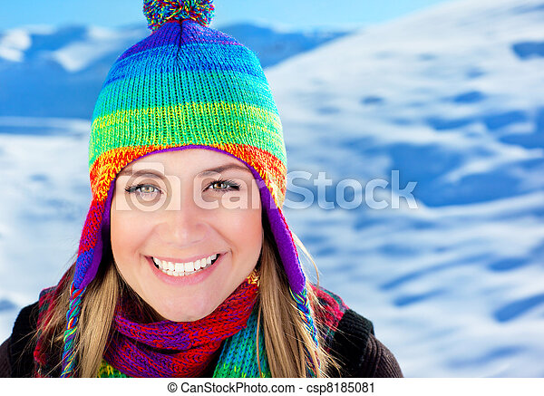 Cute girl having fun outdoor at winter mountains, closeup portrait of a beautiful smiling female face over snow, young teen tourist woman wearing colorful hat, Christmas holidays travel and vacation - csp8185081