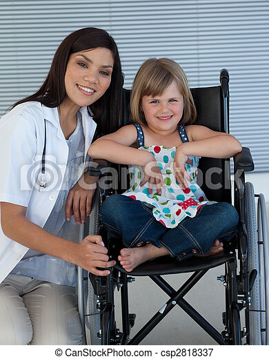 Cute girl sitting on a wheelchair with a female doctor - csp2818337
