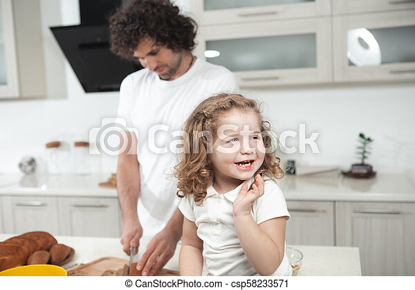 Cute girl sitting on table near her father in cook room - csp58233571