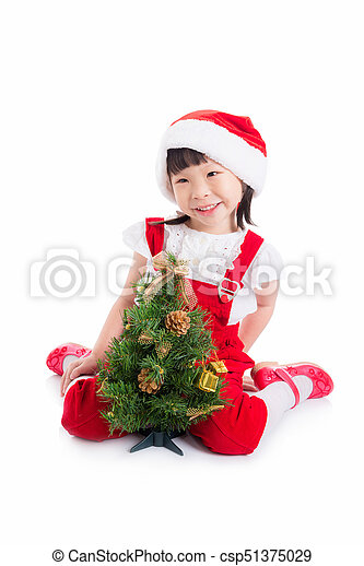 d151b184289b cute girl wearing santa dress sitting on the floor with christmas tree -  csp51375029