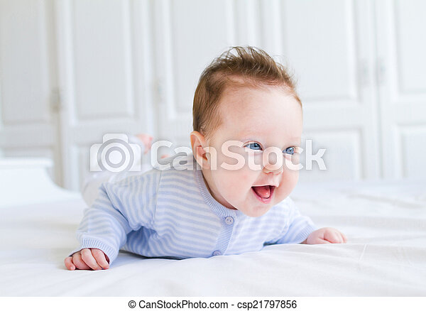 Cute laughing little baby enjoying her tummy time on a white bla - csp21797856