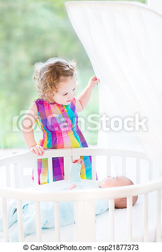 Cute laughing toddler girl playing with her newborn baby brother - csp21877373