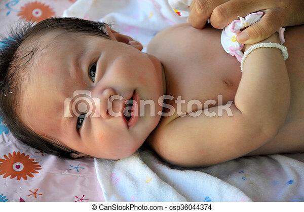 Cute little asian girl taking a bath .