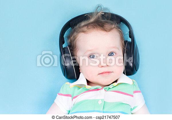 Cute little baby with huge earphones.