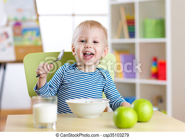 cute little boy eating cereal with the milk in nursery - csp35103279