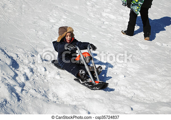 1e1d0db2c Cute little boy riding motorcyle in the snow outdoors.