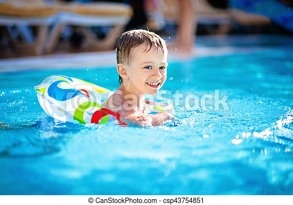 Cute little boy swimming in the pool in rubber ring fa9f3245b