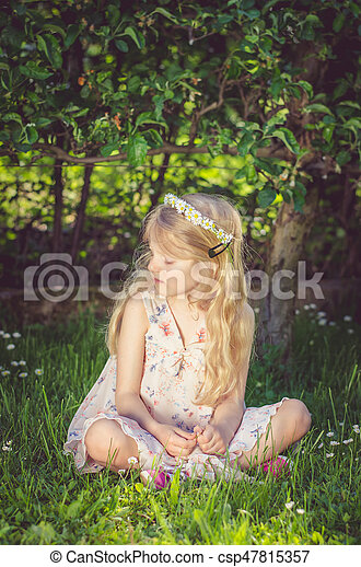 cute little child sitting in the grass - csp47815357