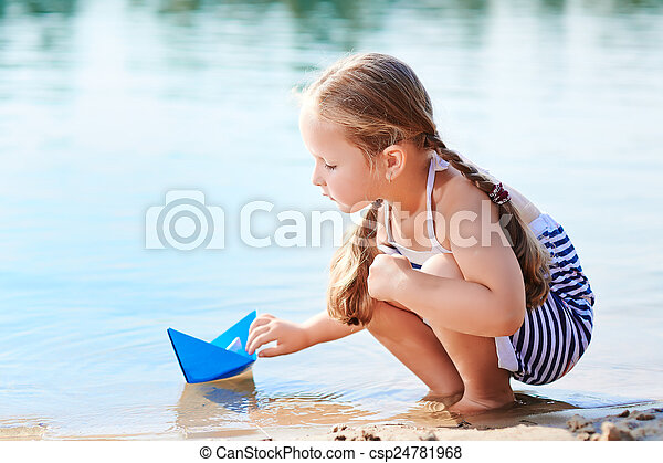 Cute little girl holding origami boat outdoors - csp24781968