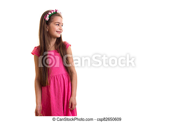 Cute little girl in pink dress at white background - csp82650609