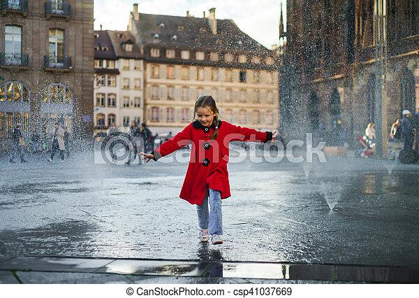 Cute little girl playing in water splash of street fountain - csp41037669