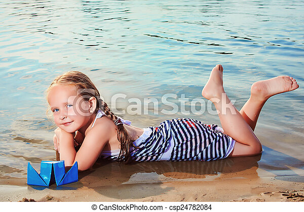Cute little girl playing origami boat. Toned image - csp24782084