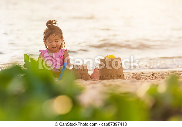 cute little girl playing sand with toy sand tools - csp87397413