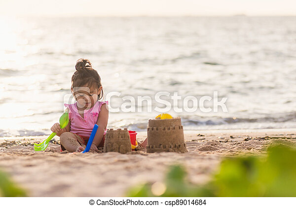 cute little girl playing sand with toy sand tools - csp89014684