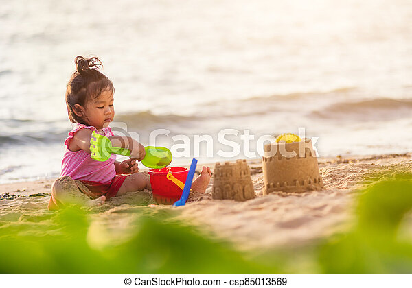 cute little girl playing sand with toy sand tools - csp85013569