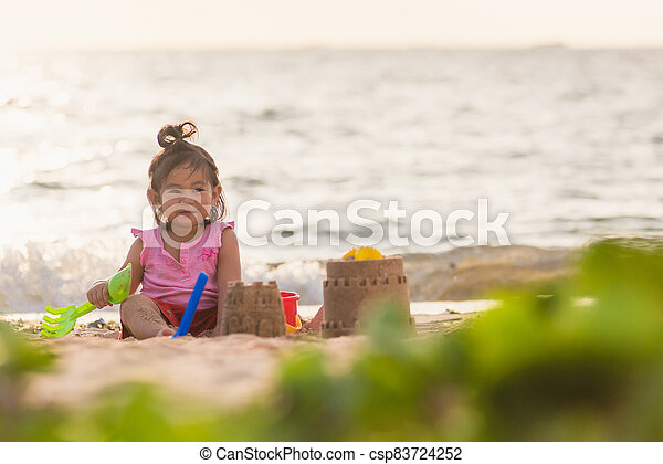 cute little girl playing sand with toy sand tools - csp83724252