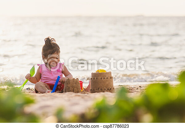 cute little girl playing sand with toy sand tools - csp87786023