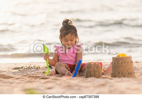 cute little girl playing sand with toy sand tools - csp87397398