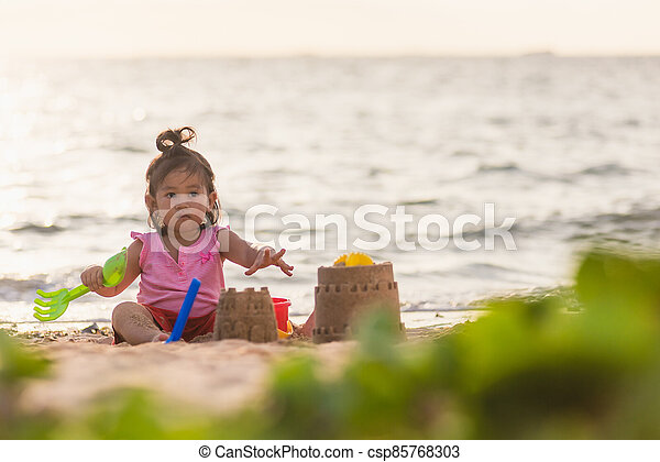 cute little girl playing sand with toy sand tools - csp85768303