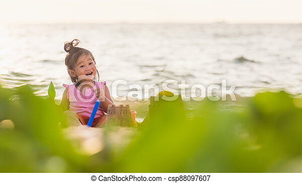 cute little girl playing sand with toy sand tools - csp88097607