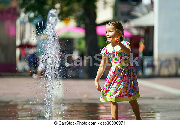 Cute little girl playing with fountain splash - csp30836371