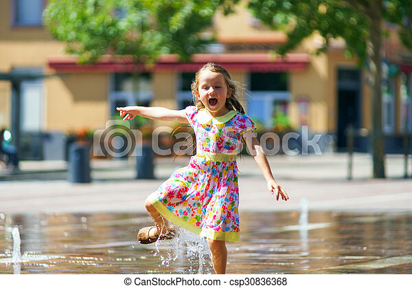 Cute little girl playing with fountain splash - csp30836368