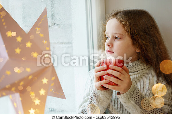Cute little girl sitting with a cup of hot cocoa by the window and looking on first falling snow - csp63542995