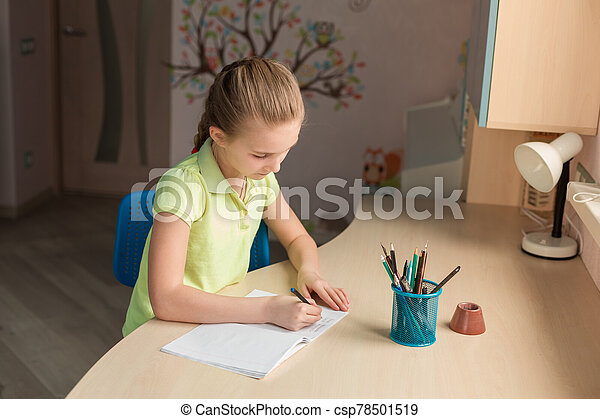Cute little girl writing her homework at the table - csp78501519