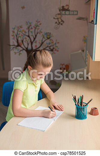 Cute little girl writing her homework at the table - csp78501525