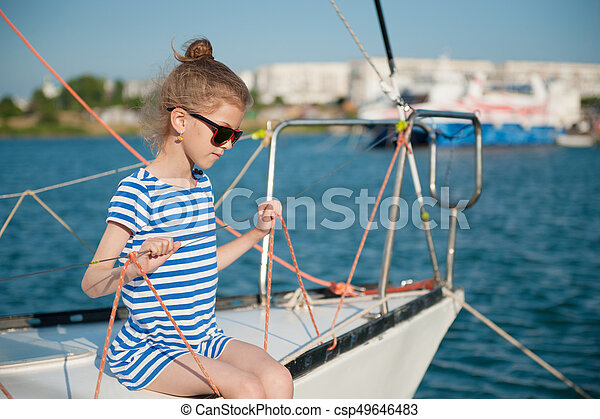 cute little healthy child in sunglasses sitting aboard luxury recreational boat - csp49646483
