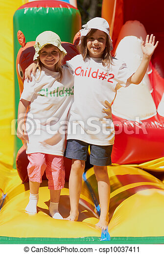 Cute little sisters in a jumping castle - csp10037411