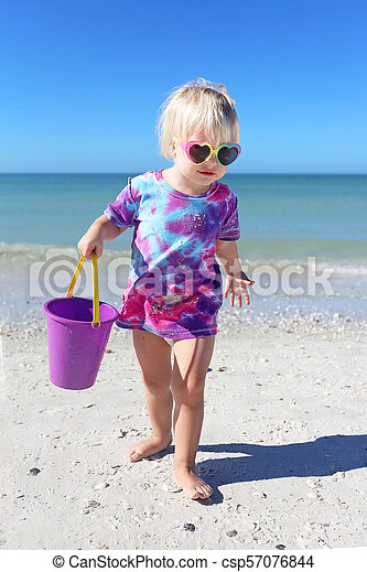 Cute Little Toddler Girl Playing on Beach by the Ocean - csp57076844