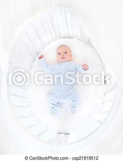 Cute newborn baby boy in a white round crib - csp21818512