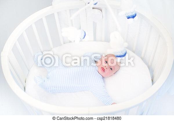 Cute newborn baby boy in a white round crib watching toys - csp21818480