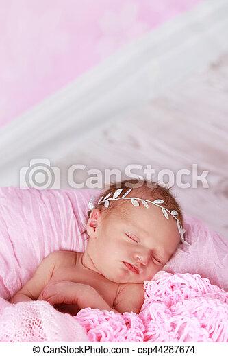 Cute newborn baby girl sleeping csp44287674