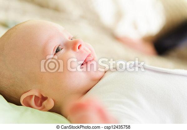 Cute newborn baby smiling in bed - csp12435758