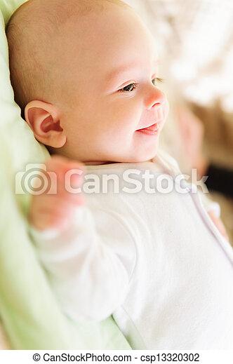 Cute newborn baby smiling in bed - csp13320302