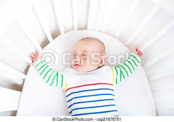 Cute newborn little boy sleeping in a white round crib - csp21878751