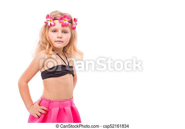 Cute pretty little girl in black bikini, pink skirt and pink wreath - csp52161834