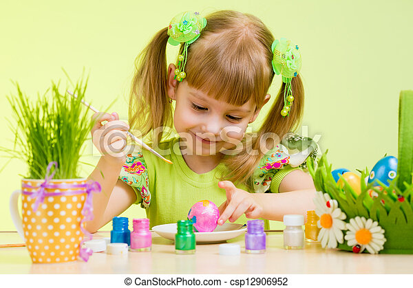 cute smiling child girl painting Easter eggs on green background - csp12906952