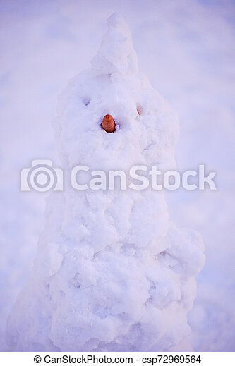cute snowy snowman in the evening at the christmas city with nobody - csp72969564