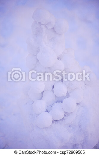 cute snowy snowman in the evening at the christmas city with nobody - csp72969565