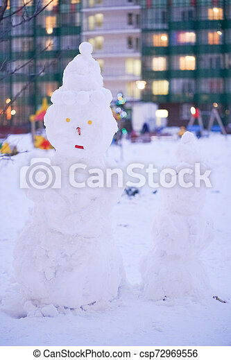 cute snowy snowman in the evening at the christmas city with nobody - csp72969556