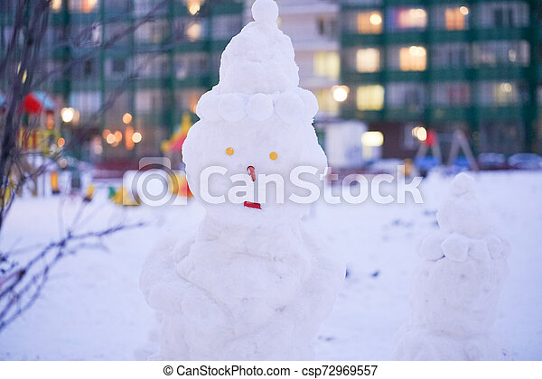 cute snowy snowman in the evening at the christmas city with nobody - csp72969557