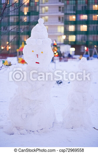 cute snowy snowman in the evening at the christmas city with nobody - csp72969558