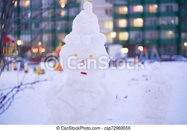 cute snowy snowman in the evening at the christmas city with nobody - csp72969559
