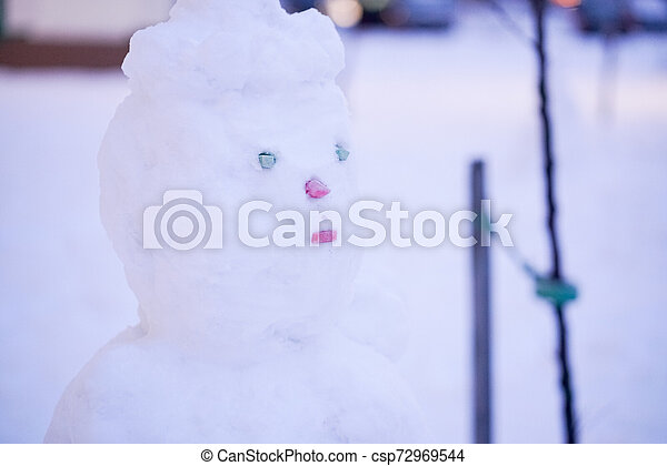 cute snowy snowman in the evening at the christmas city with nobody - csp72969544